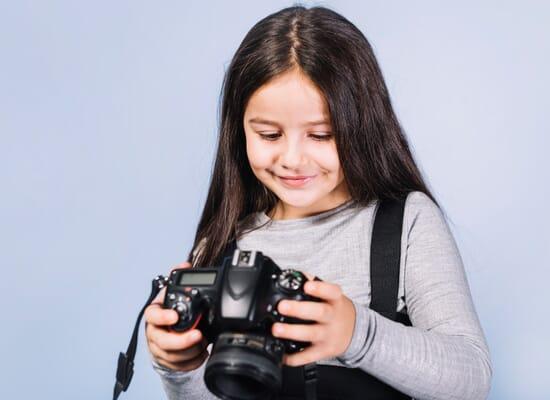 beautiful girl kid playing with camera studio photoshoot